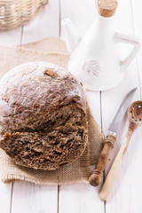 Freshly baked rye bread cob and kitchenware on wooden background
