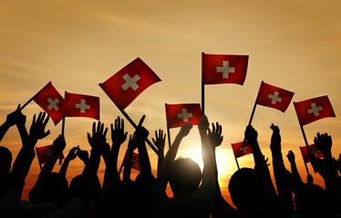 People Waving Switzerland Flags Back Lit Concept