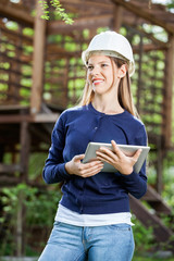 Smiling Female Architect Holding Digital Tablet At Site