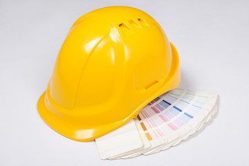 builder's yellow helmet and colorful palette over white