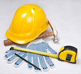 builder's tools - yellow helmet, work gloves, hammer, pen and me