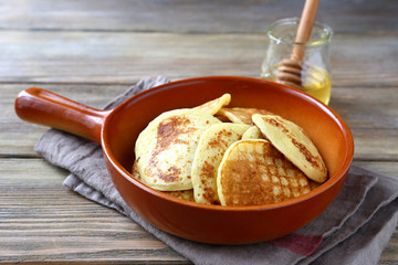 nutritious pancakes with honey on a ceramic pan