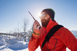 Rescue man talking with portable radio on mountain snow landscap - 79212825