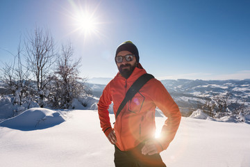Portrait of expedition man on mountain snow landscape. Back ligh
