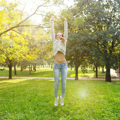 Jumping young woman outdoors in a park. Filtered image with back