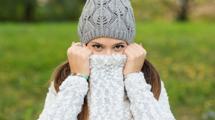 Funny portrait of young woman hiding herself in a park.