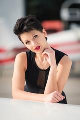 Beautiful woman fashion portrait next to airplane.