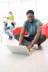 Smiling young man using laptop on floor