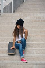 Teenager with skateboard portrait sit on the stairs.
