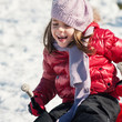 Close up of little girl sliding with bob in the snow.