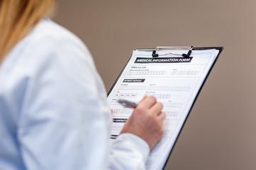 Female doctor compiling medical information form in medical cent