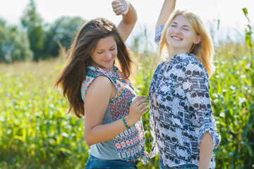 Blonde and brunette girls are dancing in farm field