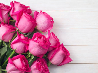 Pink roses bouquet on the white planks background