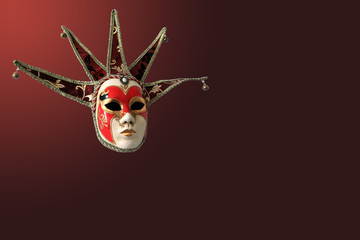 Traditional Venetian mask on burgundy background