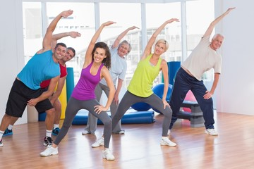 Fit people doing stretching exercise in gym