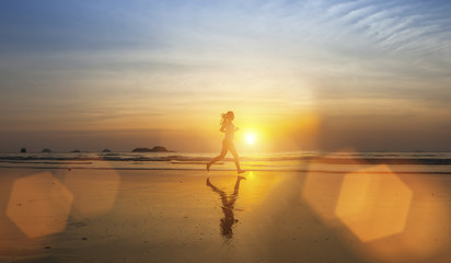 Young girl silhouette Jogging on sea beach .