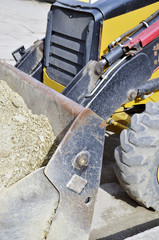 machinery at  building site. Detail Backhoe bucket with sand.