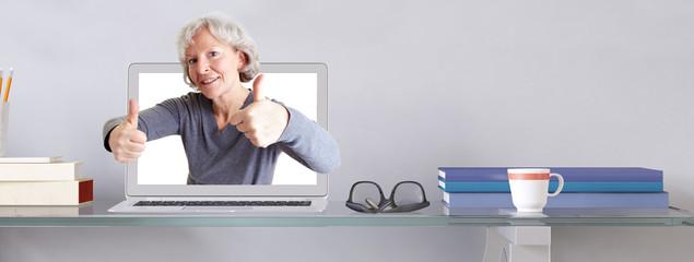 Alte Frau im Laptop hält Daumen hoch