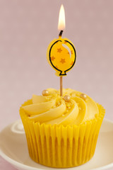 Lemon cupcake with butter cream swirl and balloon candle
