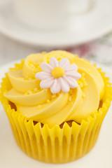 Lemon cupcake with swirl and fondant daisy flower