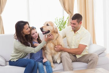 Family stroking dog while sitting on sofa