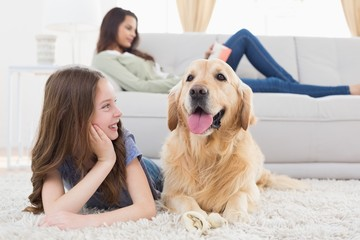 Girl looking at dog while lying on rug