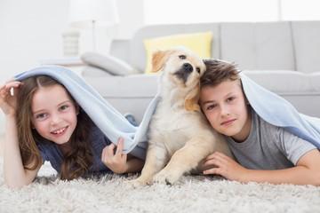 Cute siblings with dog under blanket in living room