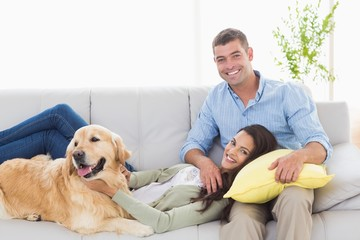 Happy couple with dog relaxing on sofa