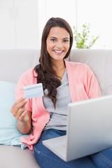 Smiling woman shopping online through laptop using credit card