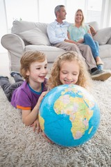 Children exploring globe while parents sitting on sofa