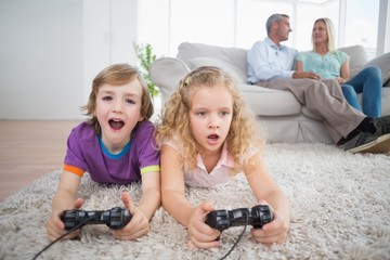 Siblings playing video game while parents sitting on sofa