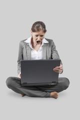 Frau sitzend vor Laptop schreiend