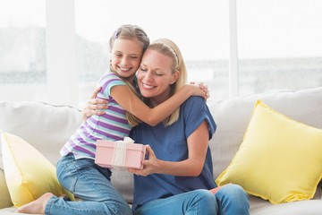 Happy mother with gift embracing daughter in house