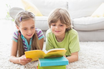 Siblings reading book while lying on rug