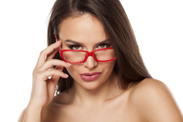 beautiful young woman looking over her glasses