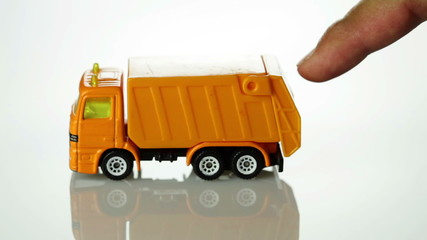 Orange toy garbage truck rolling into the scene