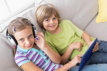 Siblings using digital tablet while listening music on sofa
