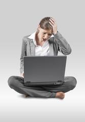 Frau mit Laptop sitzend am Boden