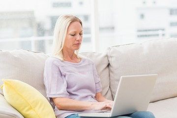 Woman using laptop white sitting on sofa