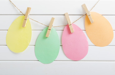 paper Easter eggs on white wooden background
