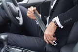 Businessman putting on his seat belt