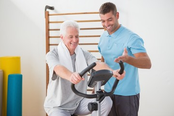 Senior man doing exercise bike with his trainer