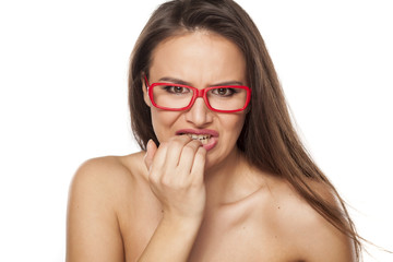 worried young woman with glasses nibbling her nails