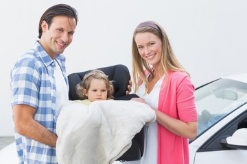 Parents carrying baby in his car seat