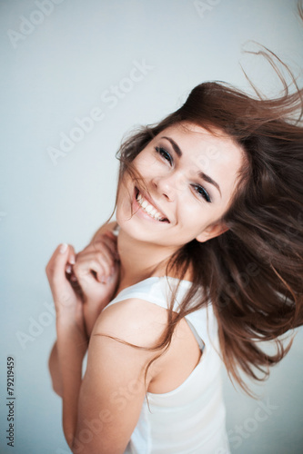 The  young girl happily laughs - 79219459