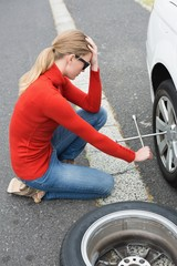 Annoyed woman trying to replace tire