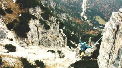 Man walking on cord in the air in mountain aerial shot