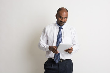 indian business male holding a computer tablet