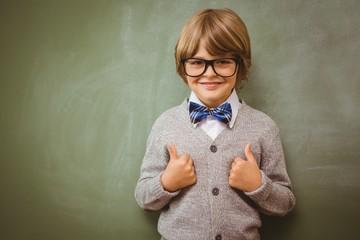Little boy gesturing thumbs up against blackboard