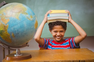Little boy holding books over head in classroom